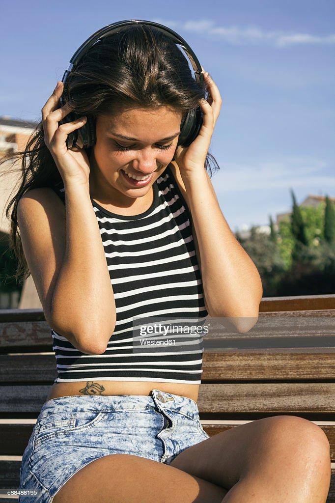 Smiling teenage girl hearing music with headphones