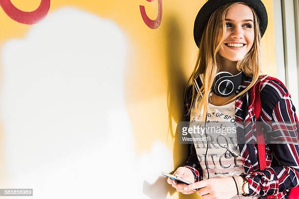 Smiling teenage girl leaning against wall