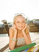 Smiling teenage girl lying on jetty