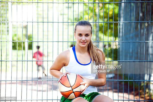 Smiling teenage girl sitting with basketball at fence