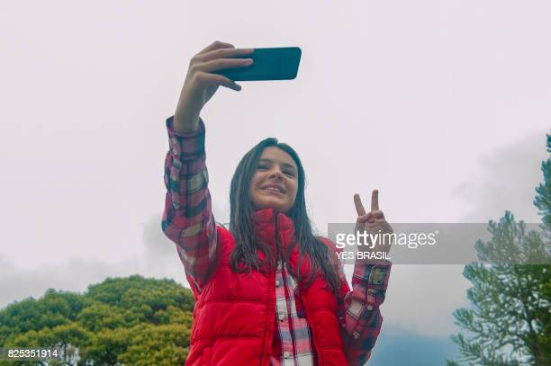 Smiling teenage girl taking selfie with cellphone