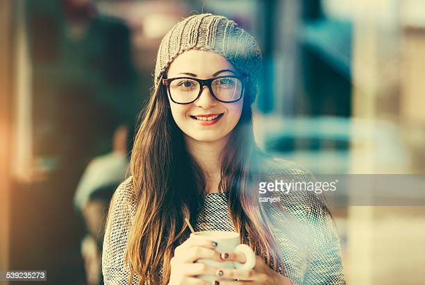 Smiling teenage girl with coffee cup portrait