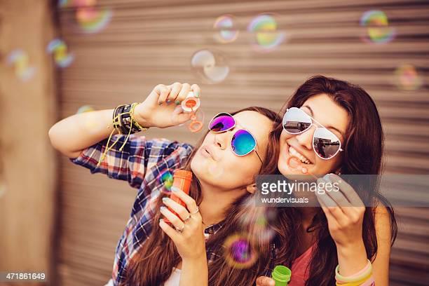 Sorridente adolescente mandar bolhas de sabão