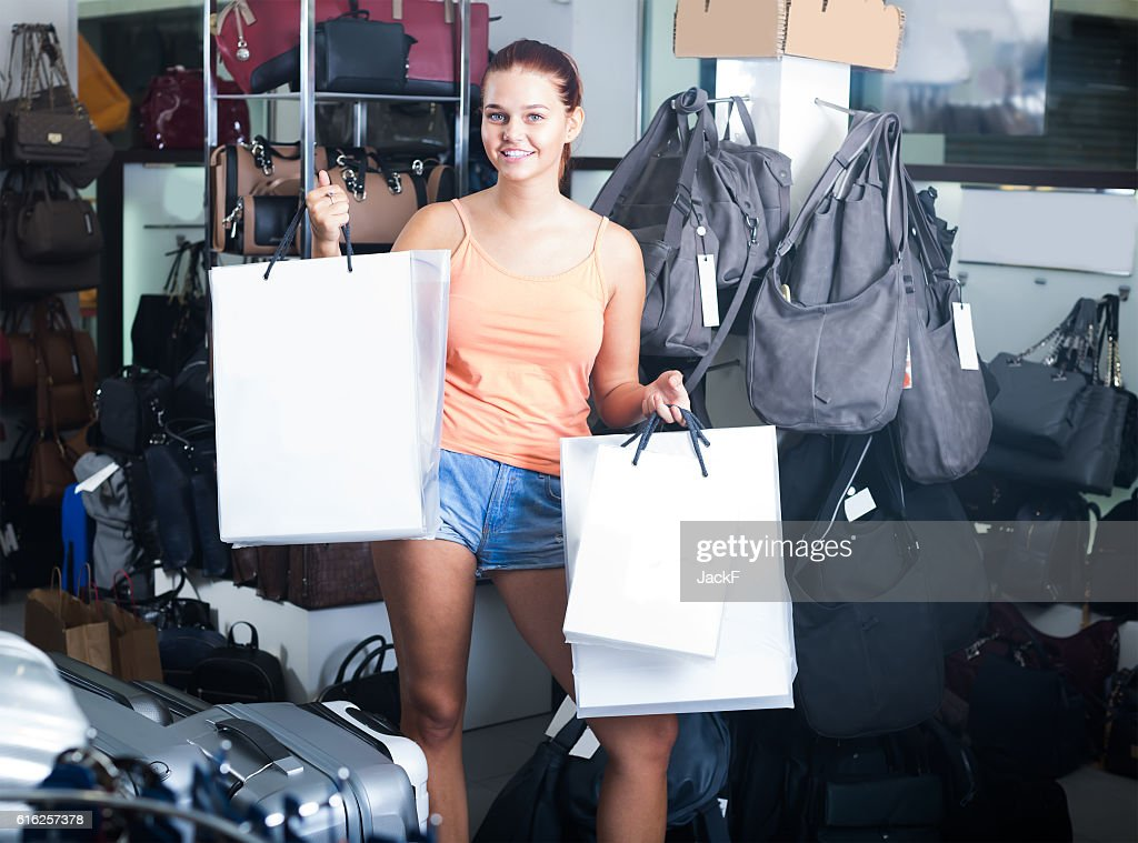 smiling teenager girl holding shopping bags in boutique : Stock Photo