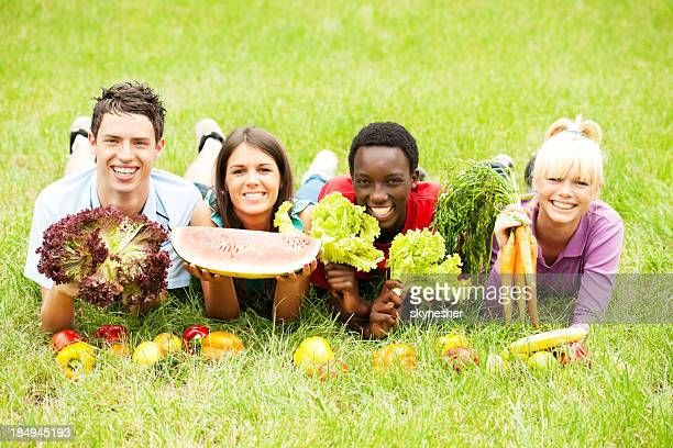 Lächelnd Teenager auf Gras liegen und holding Produkte
