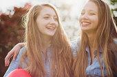 Two teen friends, having fun, holding red ballon.