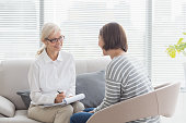Smiling therapist with woman on sofa at home