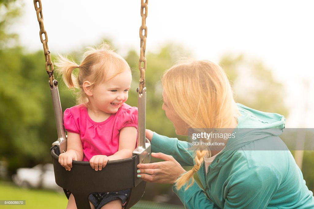 Smiling toddler girl on swing with mother