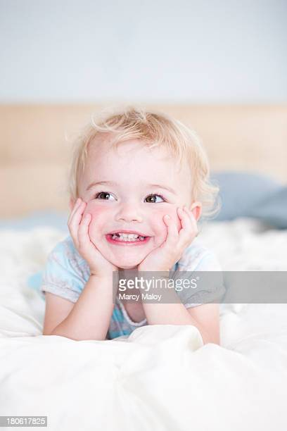 Smiling toddler girl resting her head in her hands