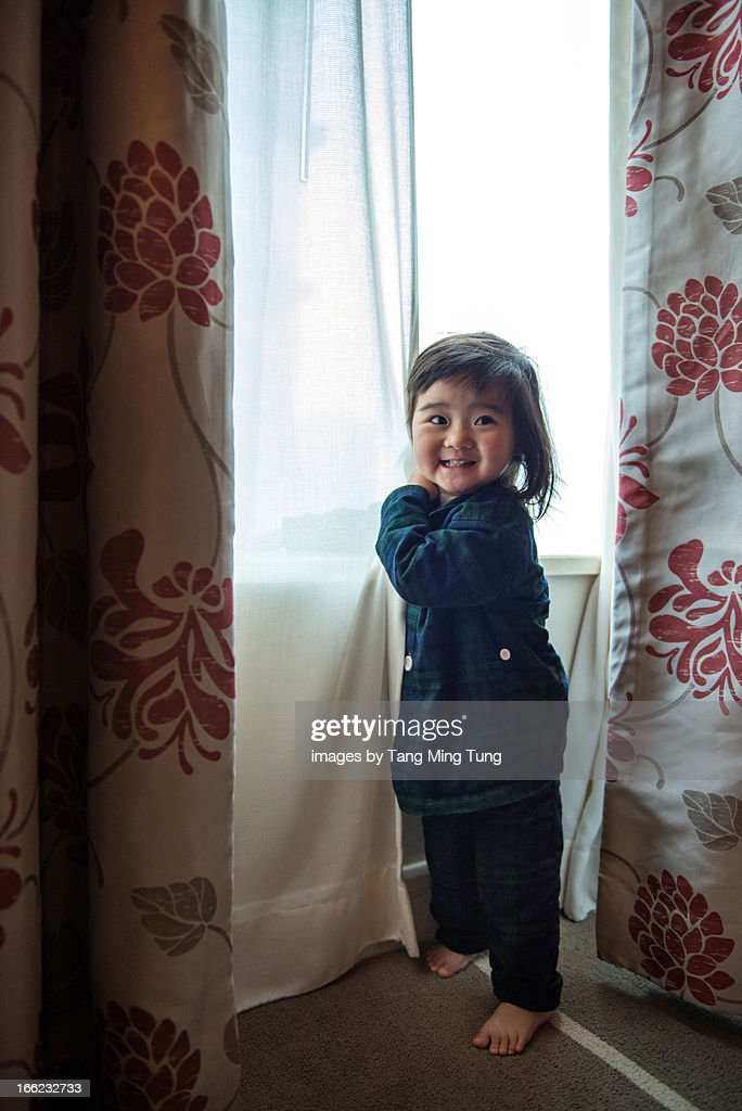 Smiling toddler girl standing next to window : Stock Photo