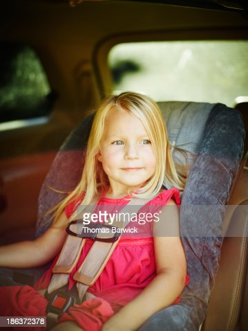 Smiling toddler sitting buckled in car seat