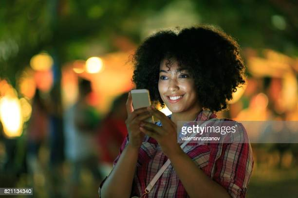 Smiling tourist using smart phone at night on street