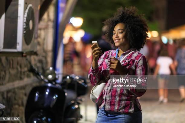 Smiling tourist using smart phone at night on street