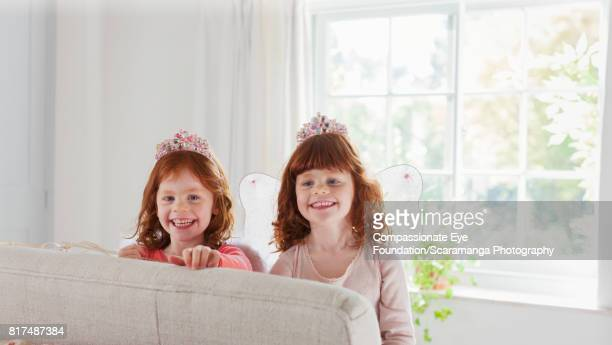 Smiling twin girls wearing fairy costumes in living room
