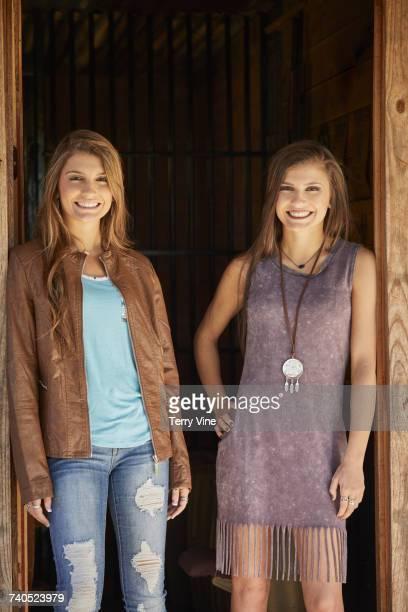Smiling twin Mixed Race teenage girls standing in doorway