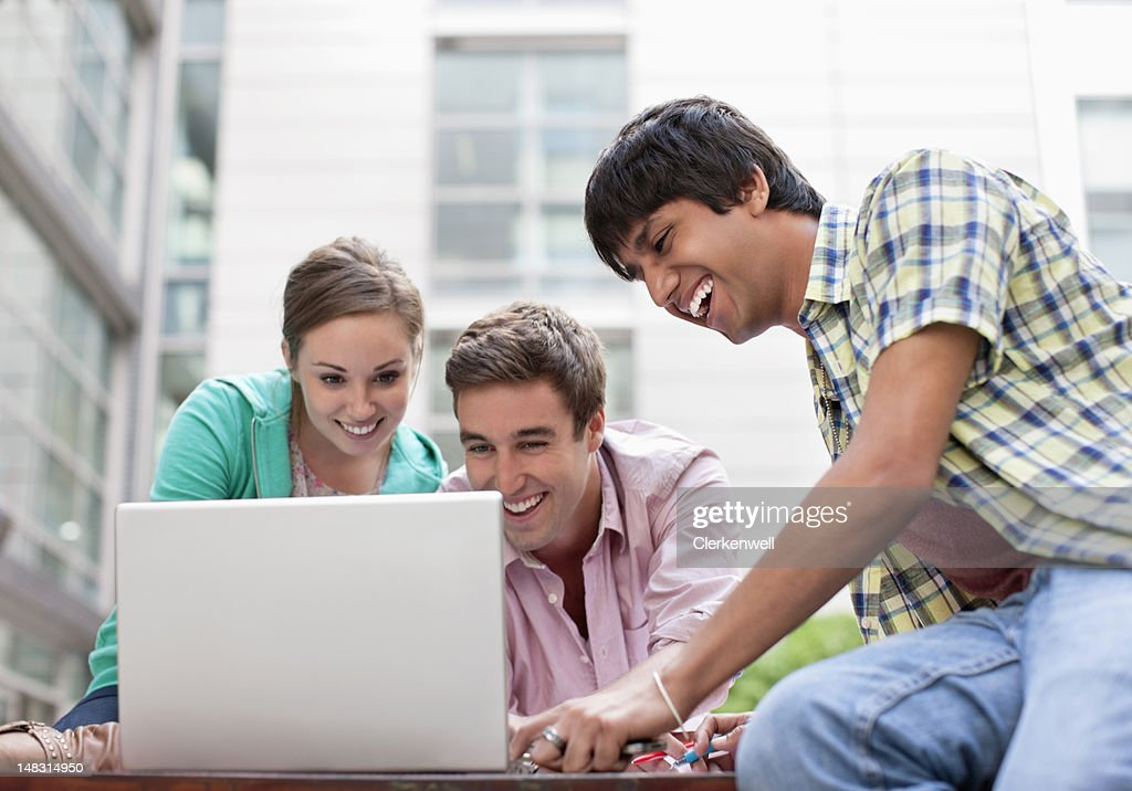 Smiling university students using laptop outdoors : Stock Photo