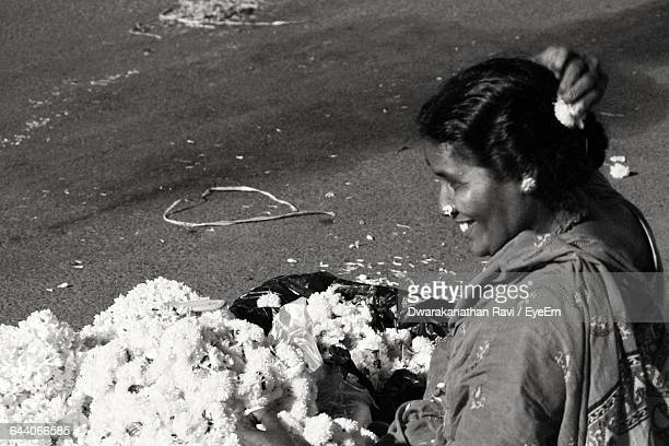 Smiling Vendor Wearing Flowers While Sitting On Street