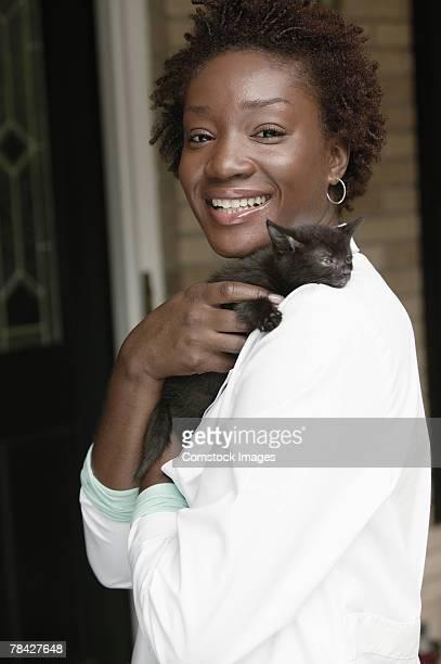 Smiling veterinarian holding kitten