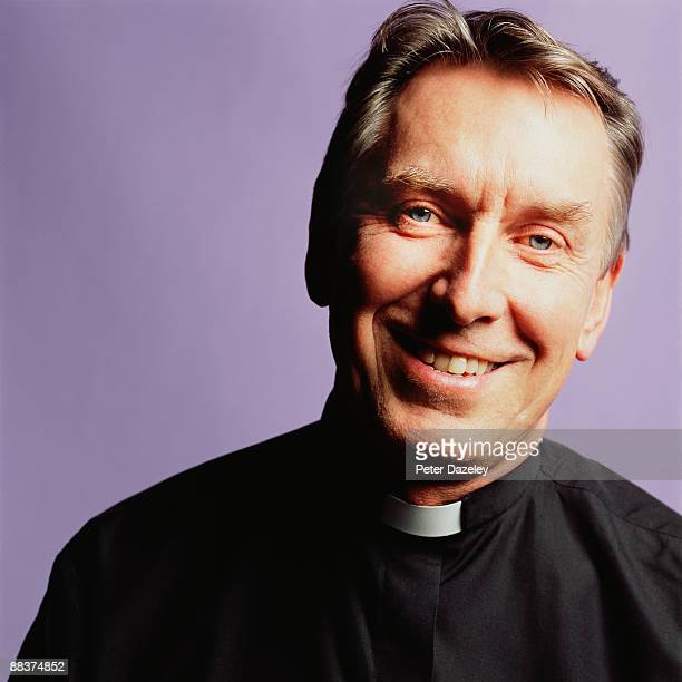 Smiling vicar with dog collar.