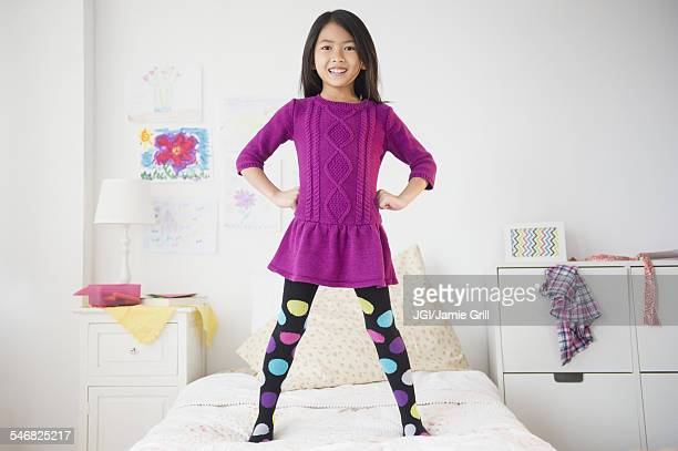 Smiling Vietnamese girl standing on bed