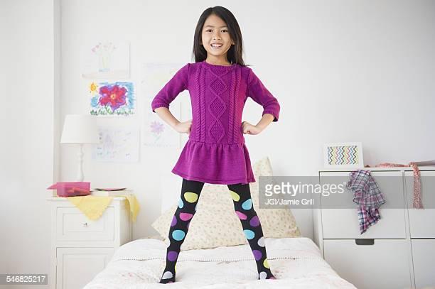 Smiling Vietnamese girl standing on bed
