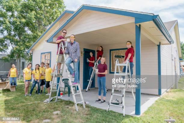 Smiling volunteers posing at house