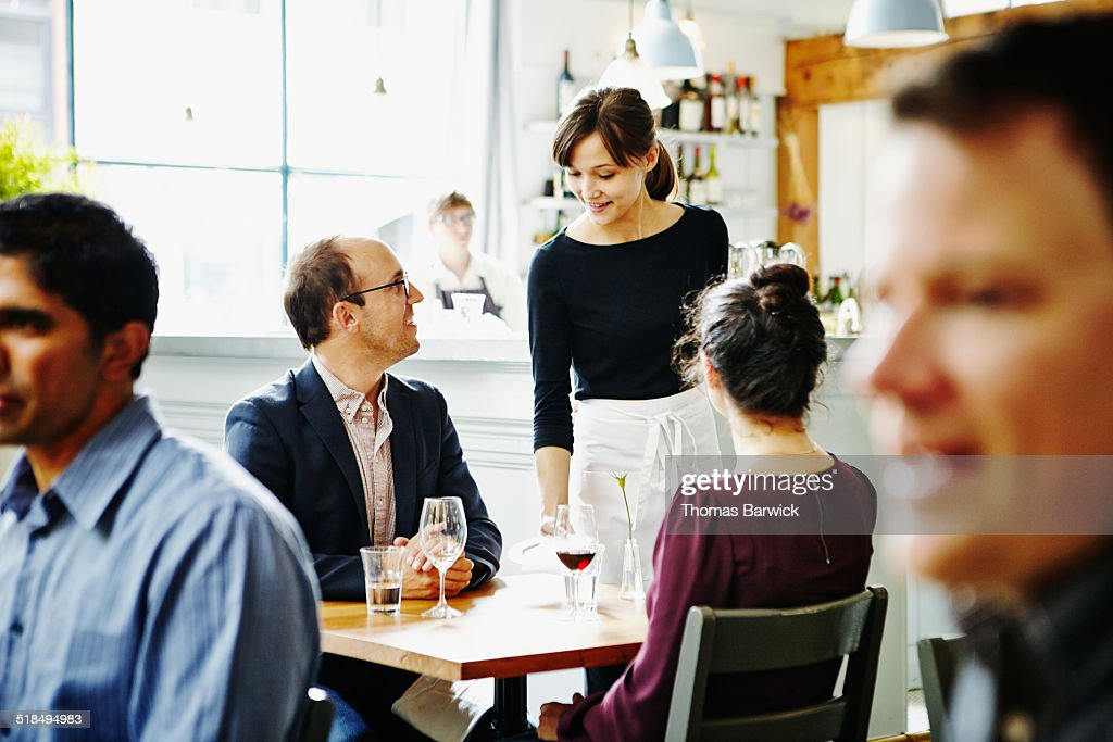 Smiling waitress delivering check to couple