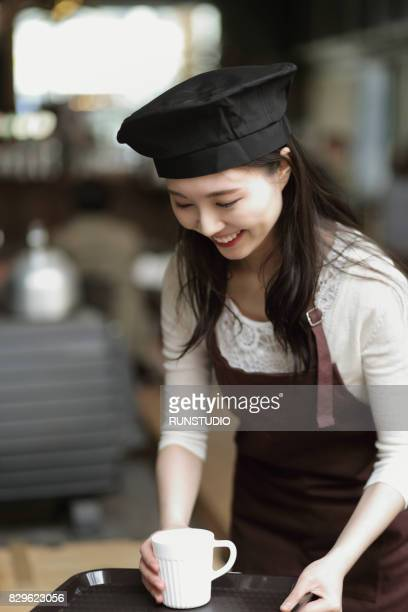 Smiling waitress serving coffee in coffee shop