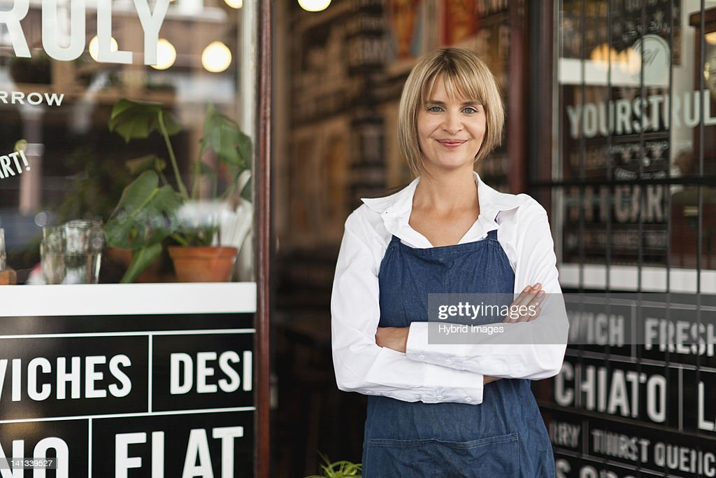 Smiling waitress standing in cafe : Stock Photo