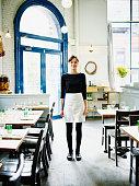 Smiling waitress standing in restaurant