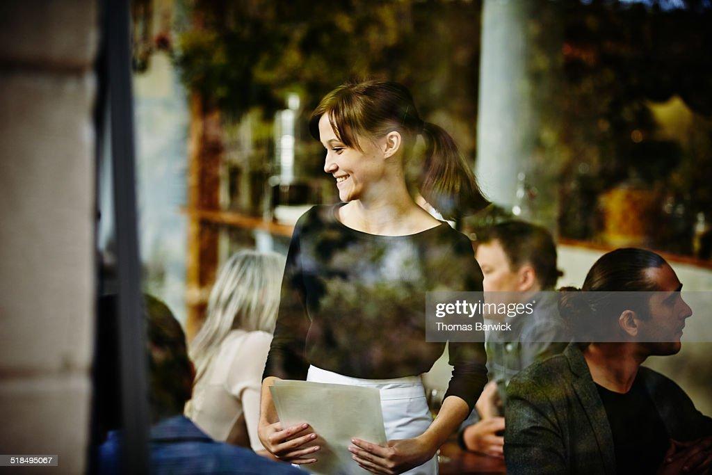Smiling waitress taking order view through window : Stock Photo