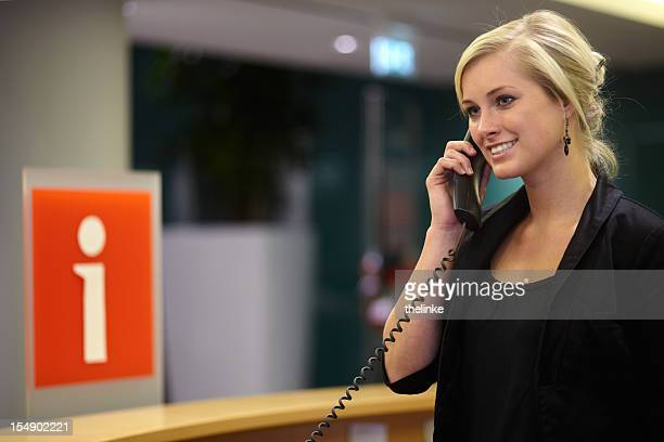 Smiling, welcoming woman on the phone at an information desk
