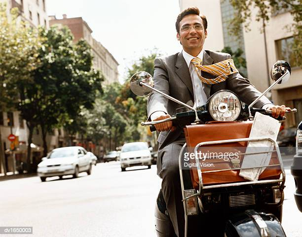 Smiling Well-Dressed Businessman Drives a Motor Scooter in the City