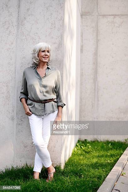 Smiling white haired senior woman leaning against concrete wall