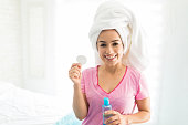 Confident woman with towel wrapped on head holding cotton pad and beauty product in bedroom