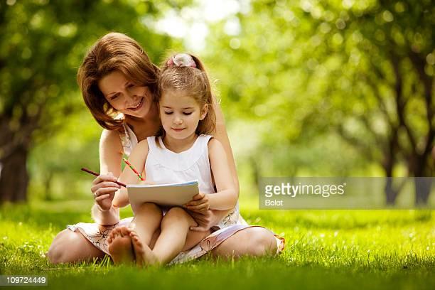 Mère et fille de dessin sur l'herbe dans le parc