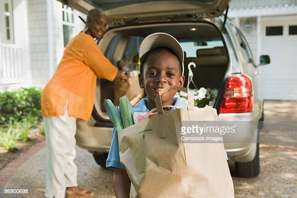 Smiling woman and boy with groceries