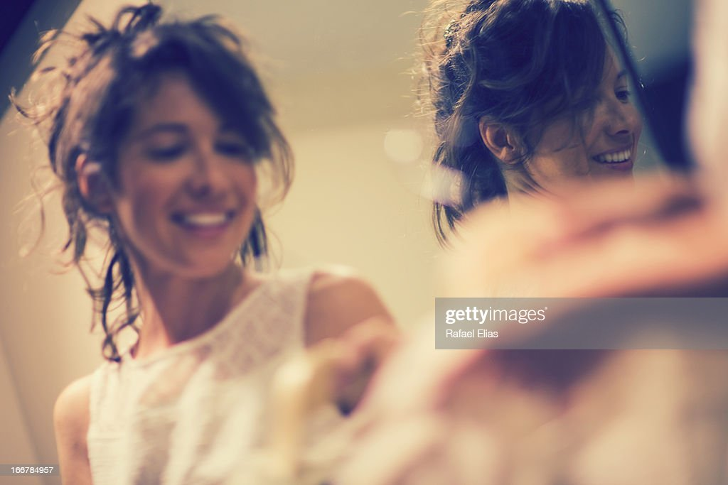 Smiling woman and her reflection in mirror : Stock Photo