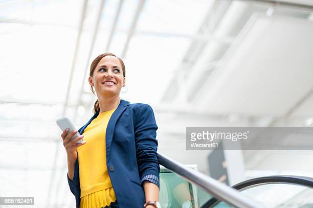 Smiling woman at a station with cell phone