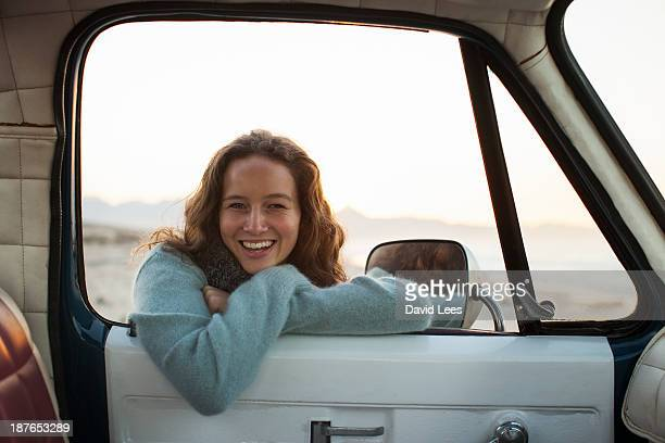 Smiling woman at beach standing by truck