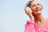 Smiling woman at beach with seashell to her ear