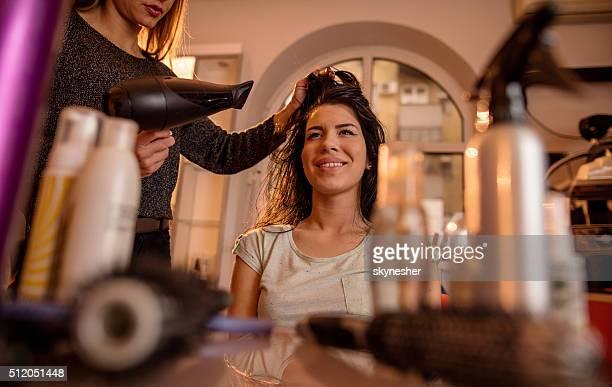 Lächelnde Frau im Friseursalon bekommen Ihr Haar getrocknet werden.