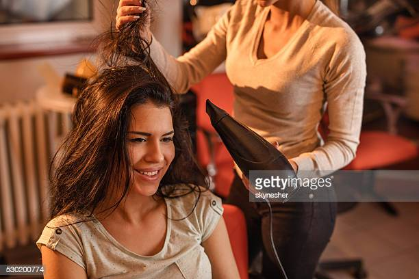 Smiling woman at hairdressers getting her hair dried.