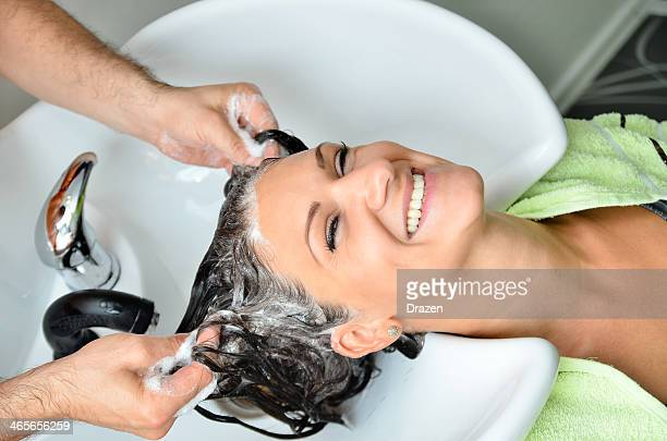 Smiling woman at hairdressers having her hair washed