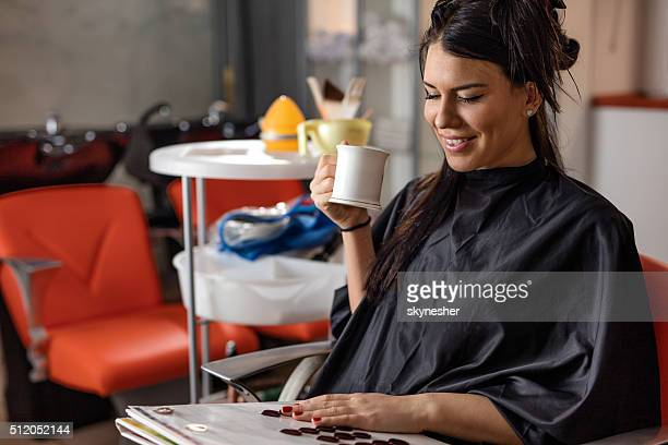 Smiling woman at hairdresser's looking at hair color palette.