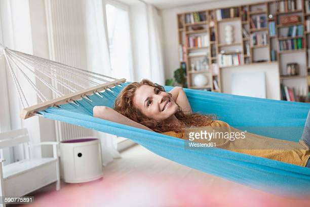 Smiling woman at home lying in hammock