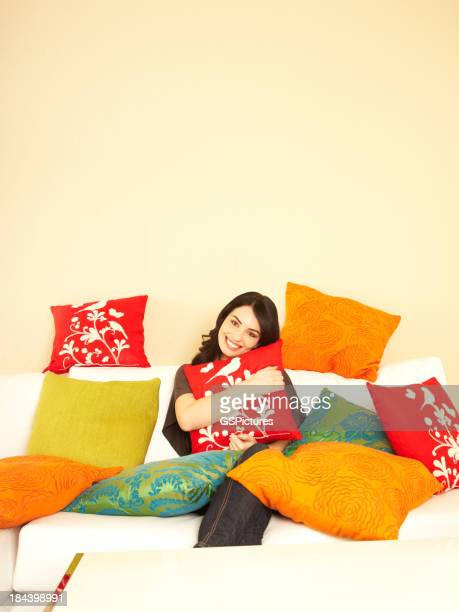 Smiling woman at home on her sofa surrounded by pillows