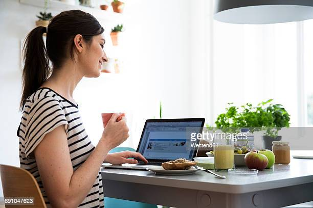 Smiling woman at home sitting at table using laptop
