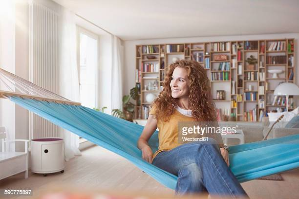 Smiling woman at home sitting in hammock