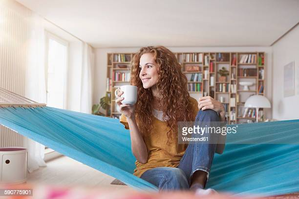 Smiling woman at home sitting in hammock with cup of coffee